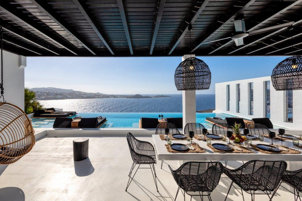 inner terrace with knitted chairs and long table with stunning view of sea horizon