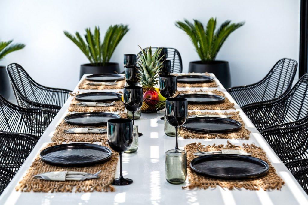 set up dinning table with vase plants in the background