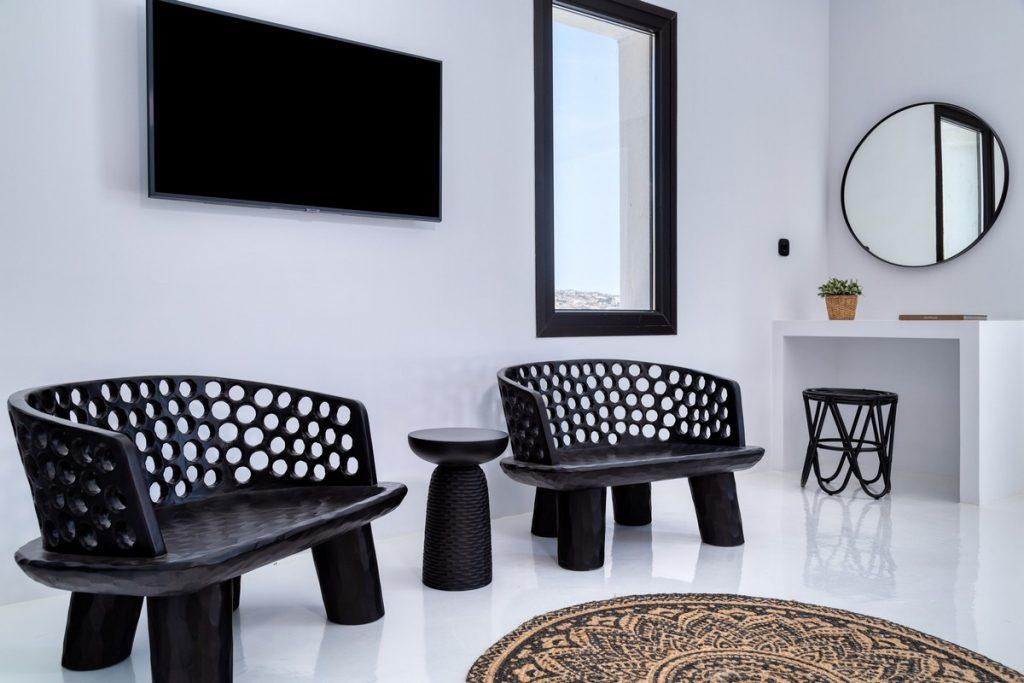 marble tiled bright living space with wall mount TV lowered interestingly designed chairs and small table