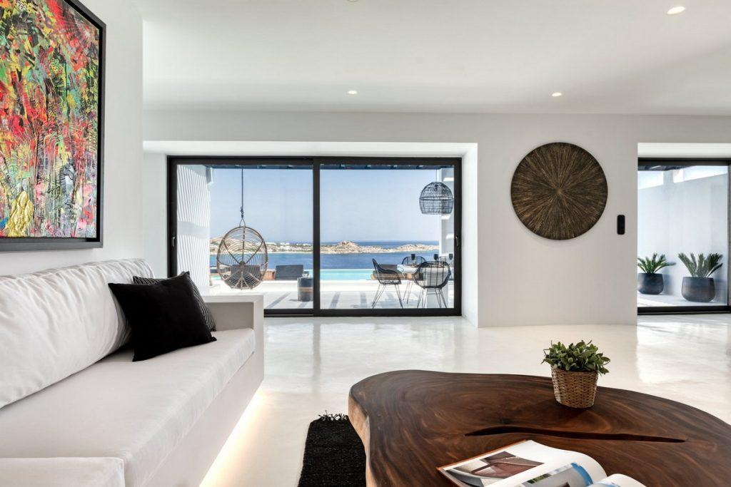 spacious living room with big sofa and wooden table faced directly at window wall sea view
