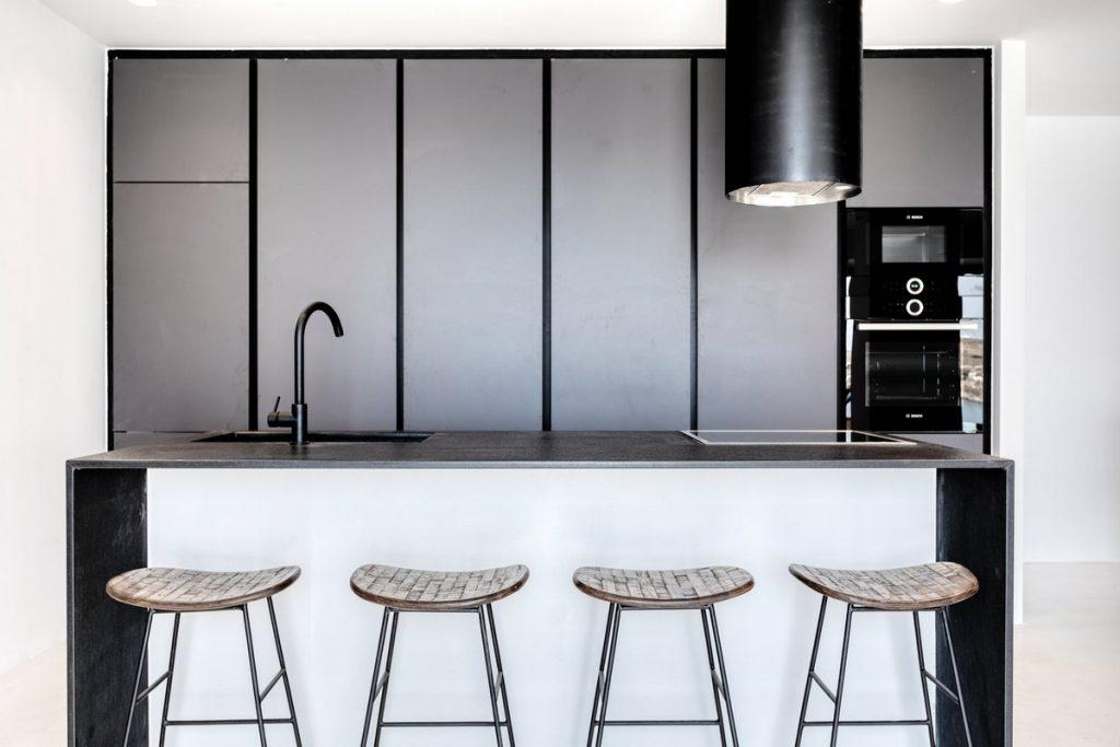 fully equipped applied layout kitchen with white table elevated bar stool chairs