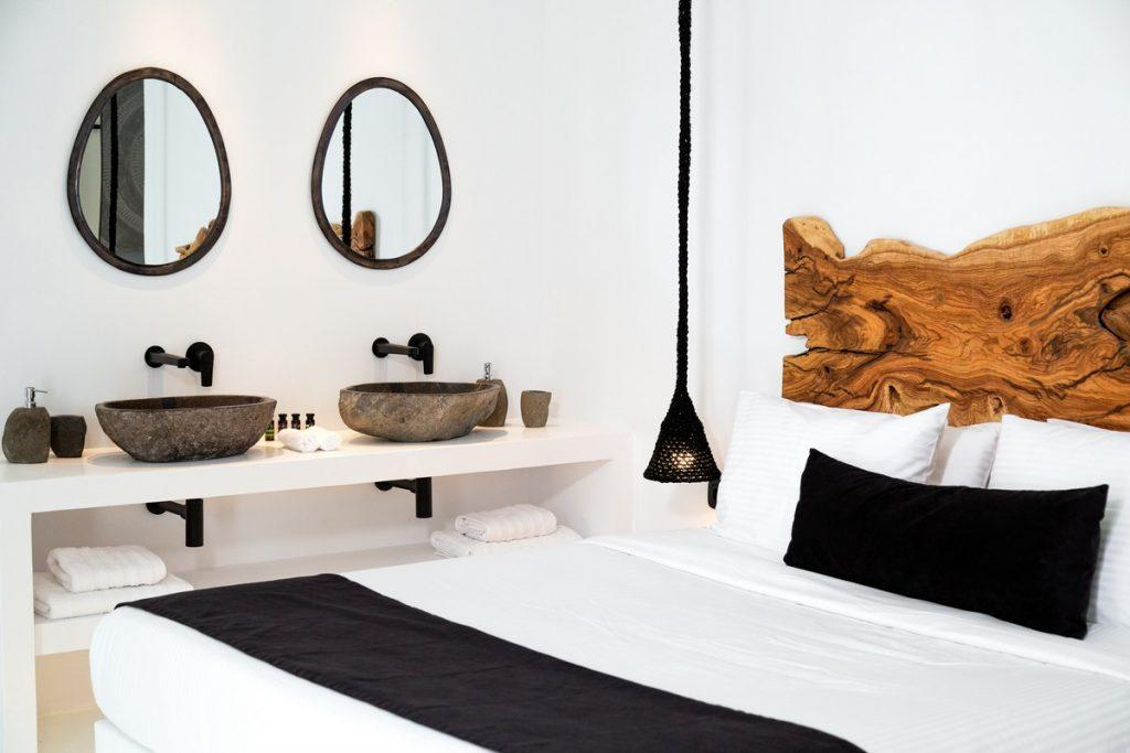 snug and cozy bedroom containing king size bed and two elevated sink and round mirrors