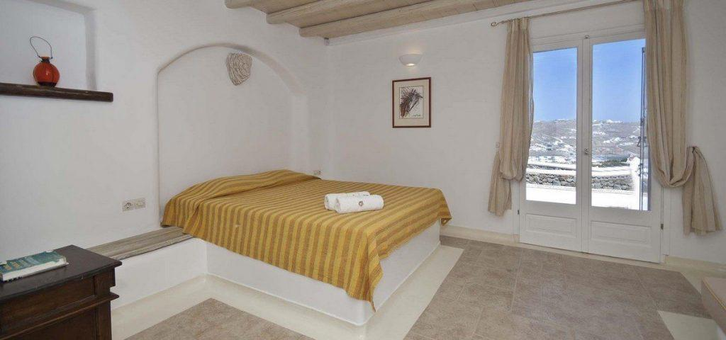 bedroom with tiled floor and yellow bed sheets