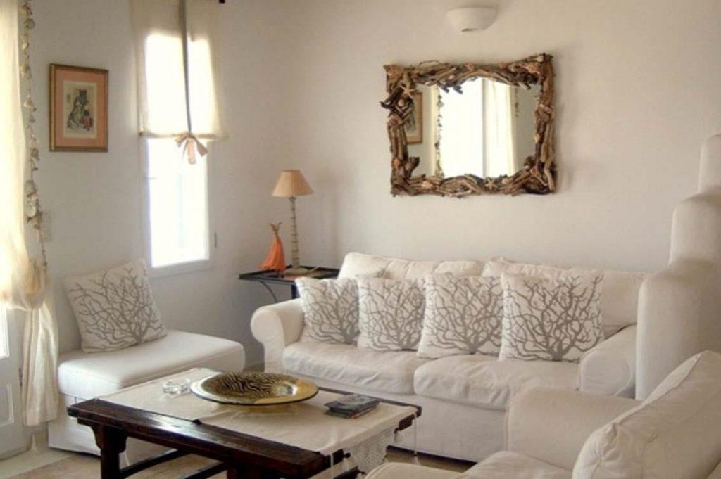 white wall living area with unique wooden mirror frame and table