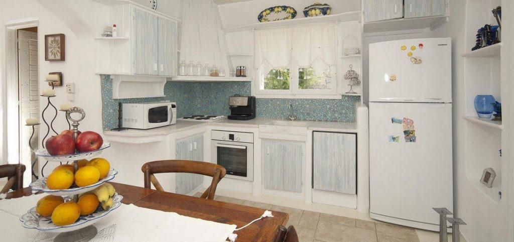 kitchen with huge white fridge and wooden cabins