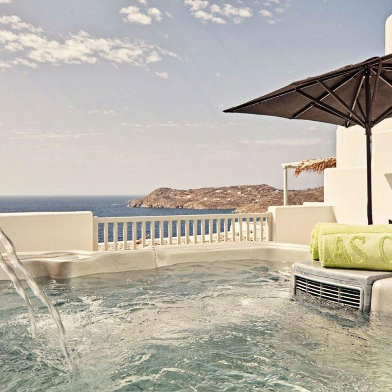 outdoor area with black umbrella and jacuzzi to relax in