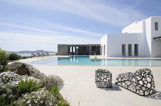 Villa Elizabeth, Aleomandra, Mykonos, exterior, white buildings, stone walls, swimming pool, porch, sunbeds, decorative chairs, coffee table, nature, plants, flowers, panoramic sea view