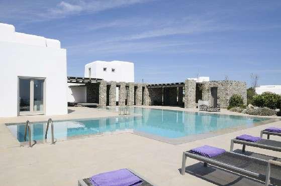 Villa Elizabeth, Aleomandra, Mykonos, white buildings, stone walls, swimming pool, sunbeds, nature, bushes, blue sky