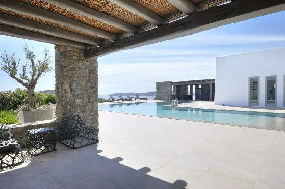 Villa Elizabeth, Aleomandra, Mykonos, outdoor rest area, porch, stone walls, chairs, swimming pool, sunbeds, panoramic view, blue sky