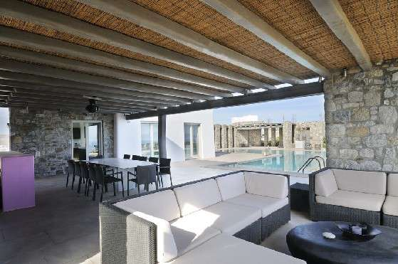 Villa Elizabeth, Aleomandra, Mykonos, porch, outdoor rest area, sofa, coffee table, dining table, chairs, wooden ceiling, stone walls, swimming pool