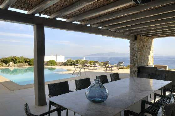 Villa Elizabeth, Aleomandra, Mykonos, porch, stone walls, dining table, woven chairs, swimming pool, sunbeds, nature, bushes, panoramic sea view