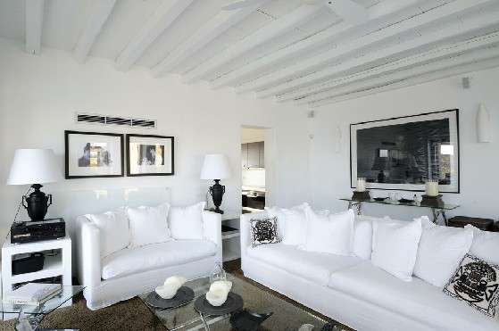 Villa Elizabeth, Aleomandra, Mykonos, white living room, sofa, pillows, coffee table, paintings, candles, night lamp, gramophone