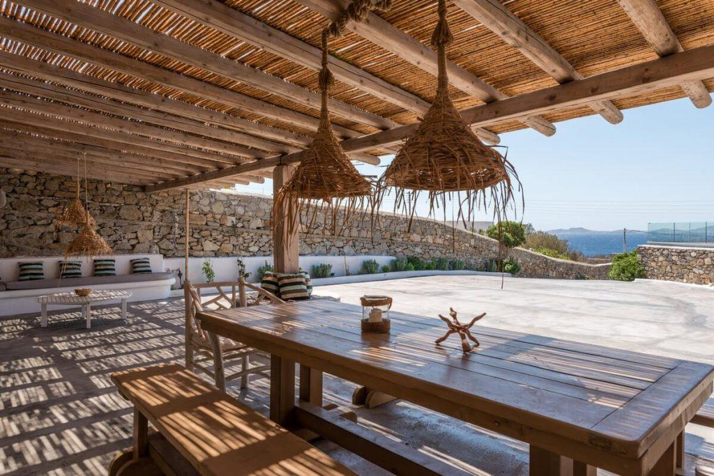 outdoor area with huge wooden table and lamps