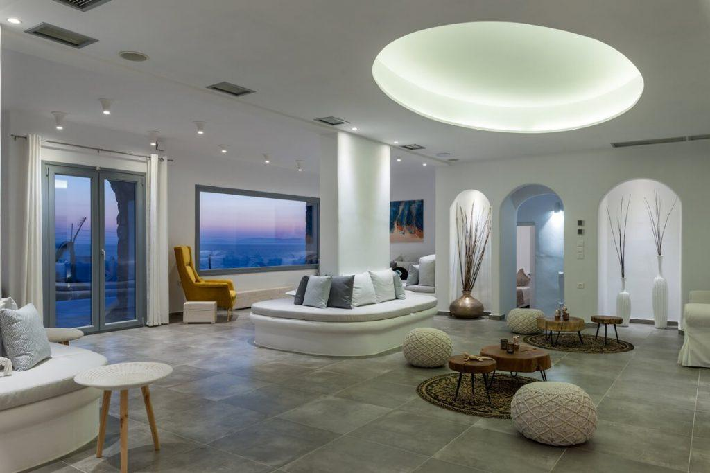 spacious living area with tiled floor and wall lamps