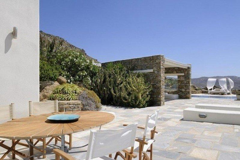 outdoor area with round wooden table and chairs