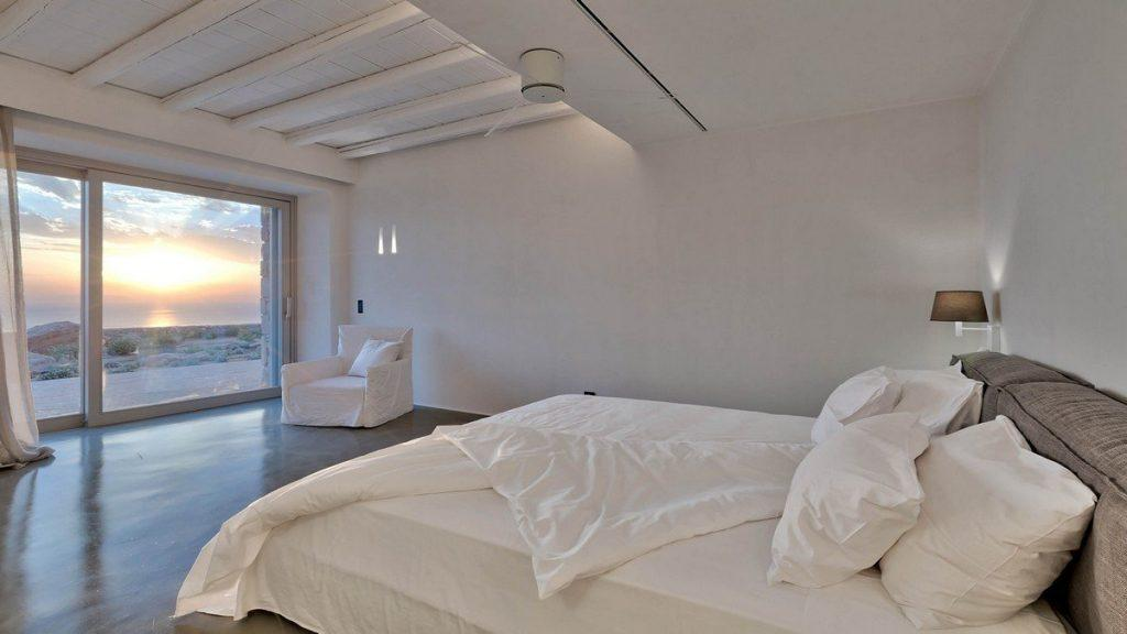 Villa Aphrodite, Agia Sofia, Mykonos, bedroom, queen size bed, panoramic window, curtains, wooden ceiling, night lamp, armchair