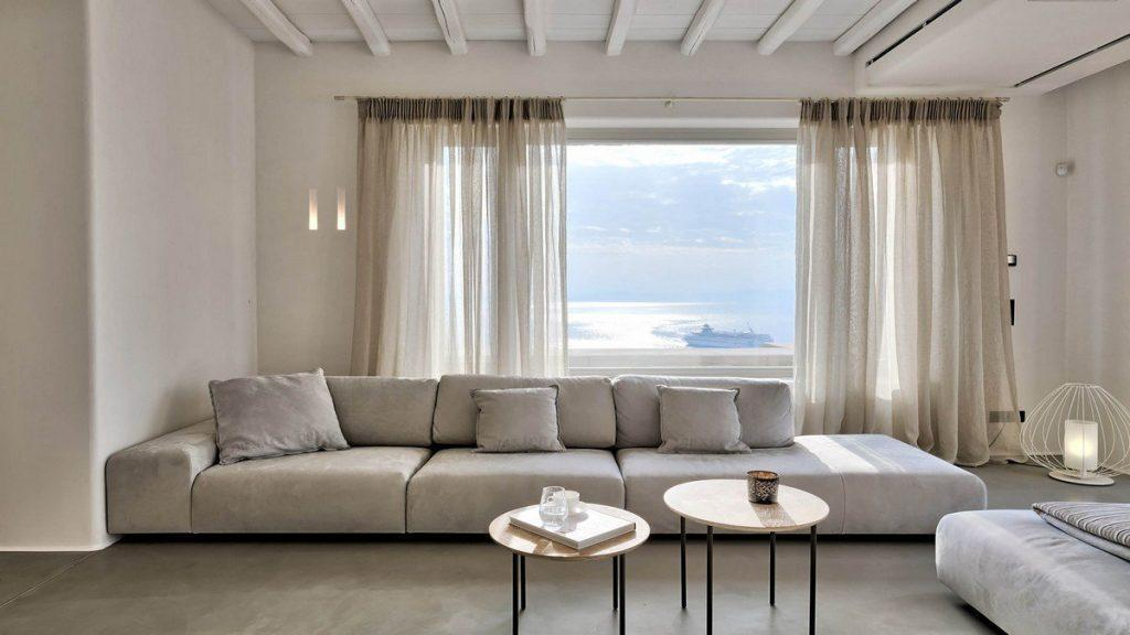 Villa Aphrodite, Agia Sofia, Mykonos, white lounge, coffee table, panoramic window, curtains, wooden ceiling