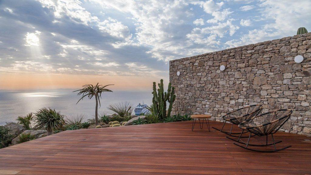 Villa Aphrodite, Agia Sofia, Mykonos, deck, chairs, coffee table, stone wall, nature, palm tree, panoramic sea view