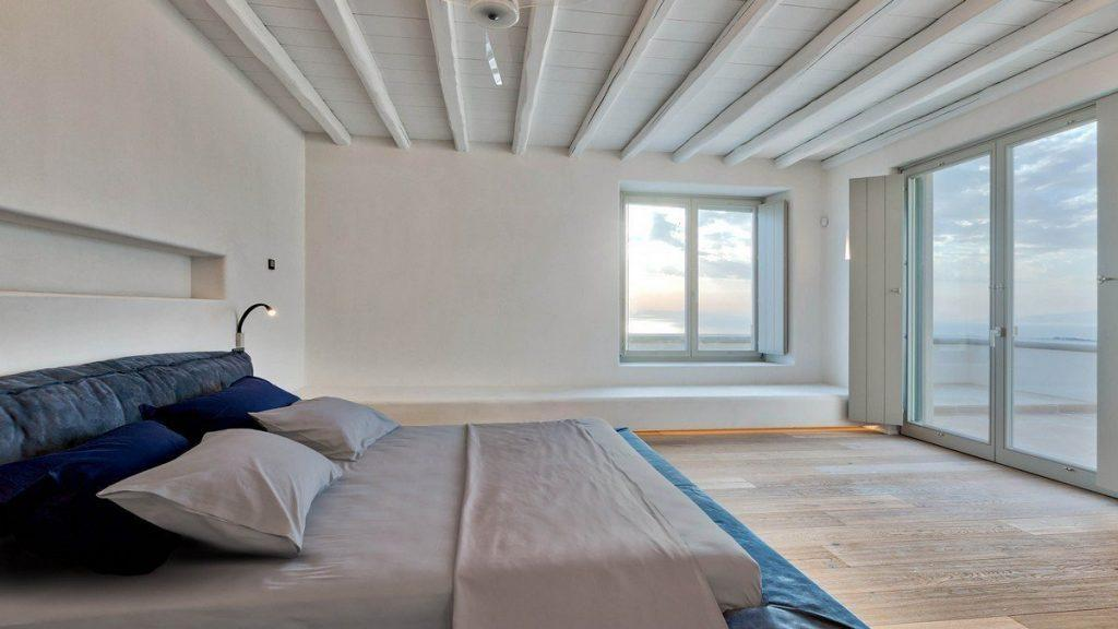 Villa Aphrodite, Agia Sofia, Mykonos, bedroom, queen size bed, pillows, night lamp, wooden ceiling, balcony doors, panoramic view