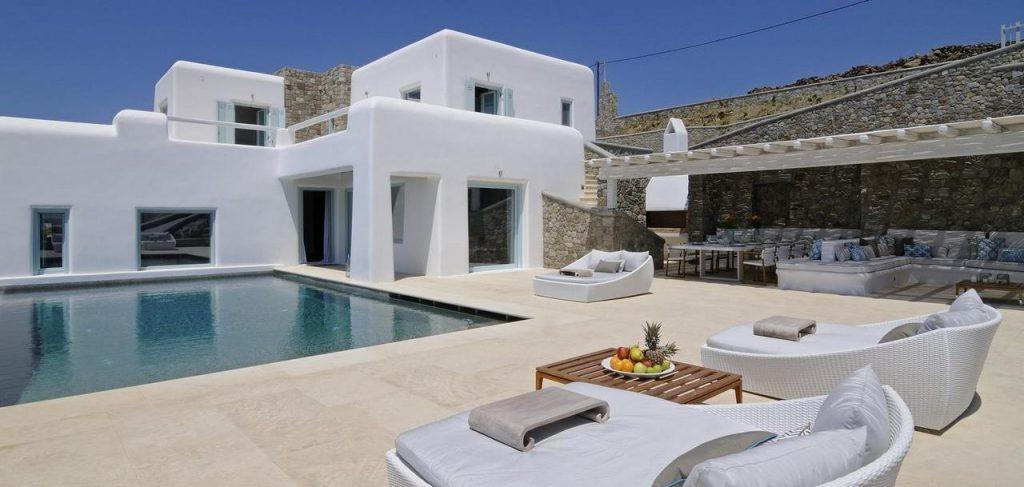 outdoor area with cozy sunbeds for you to relax with your partner or take a dip in the pool