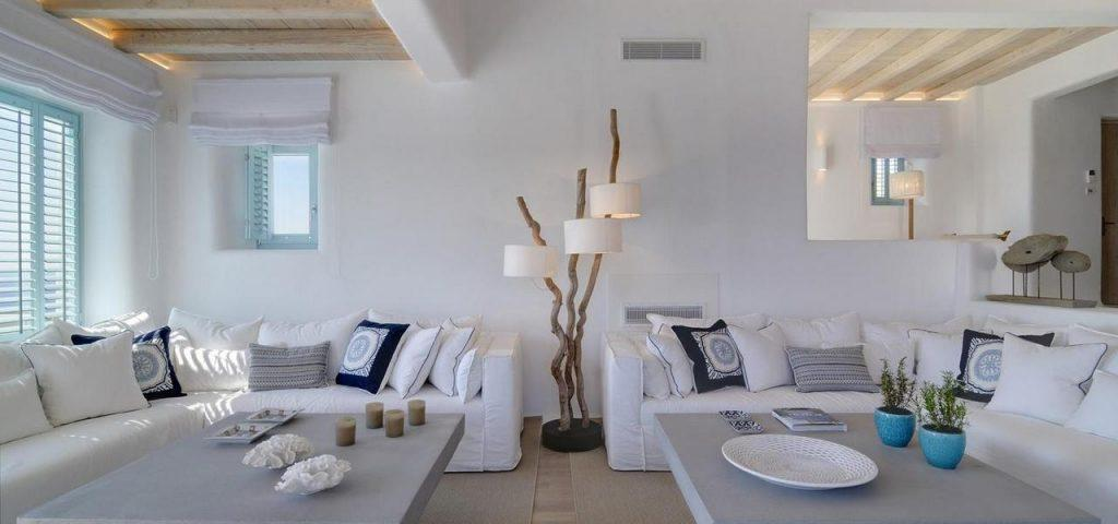 spacious white painted living room with big corner sofas extra cushions and interestingly designed lamp