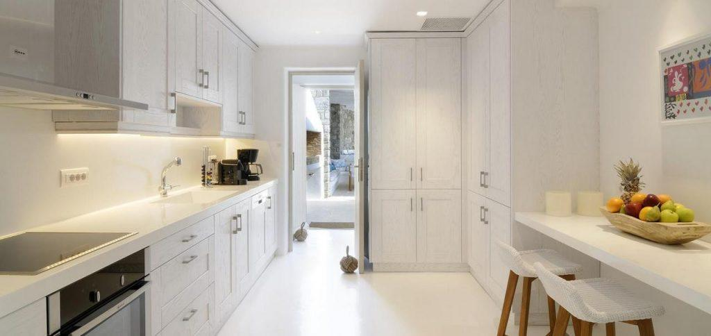 fully equipped applied layout kitchen with white table elevated wooden bar stool chairs