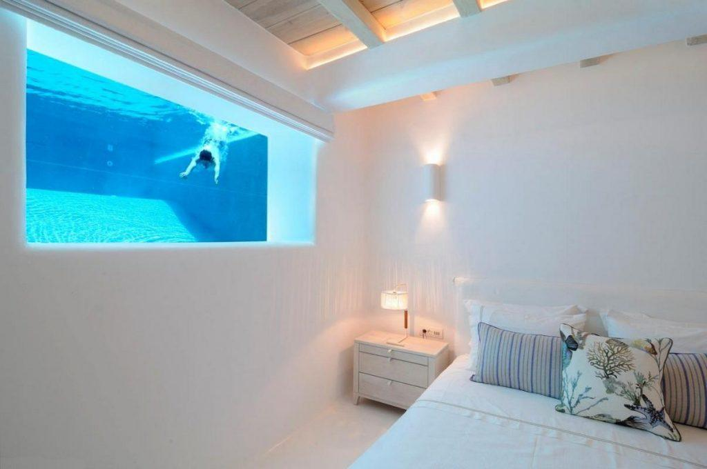 snug and comfy master bedroom with nightstand and pool window