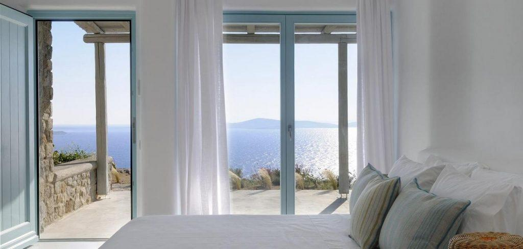 wide double bed facing window walled sea view and balcony