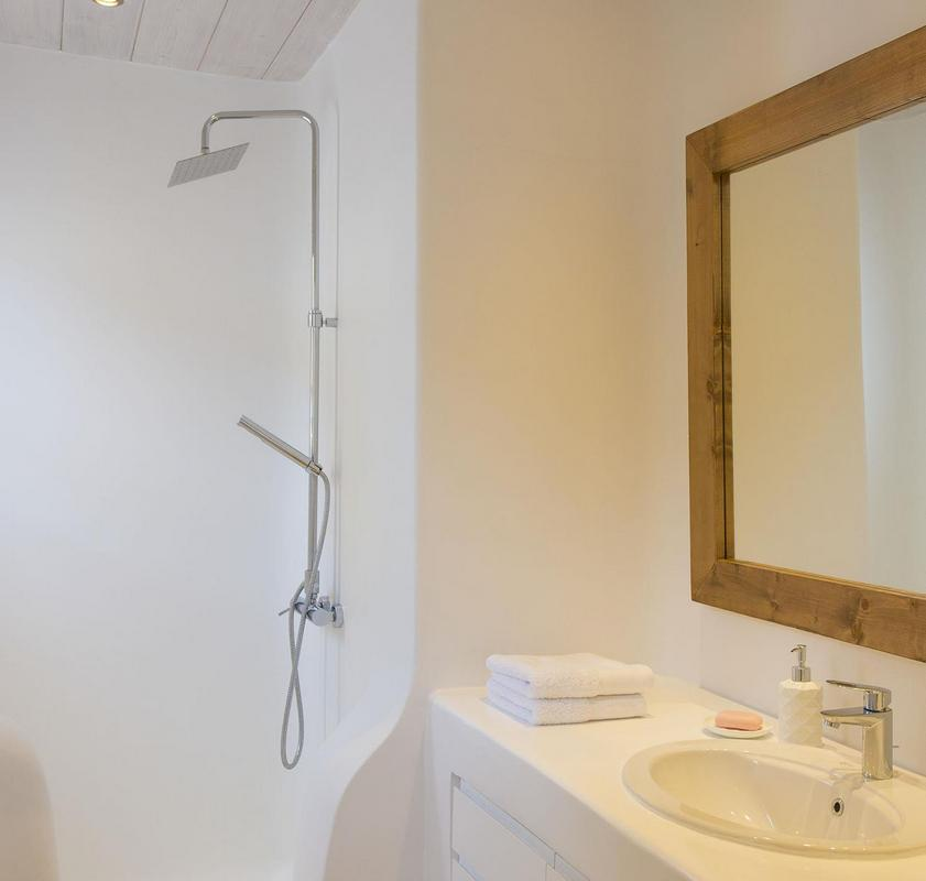 white bathroom walls with wooden frame mirror and sink