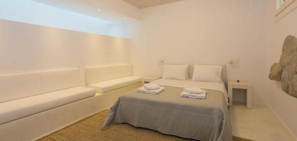 spacious bedroom with white walls and decorative stone on the wall