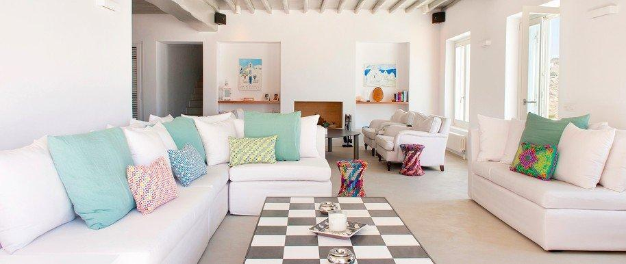 Grand House Villa Tourlos Mykonos Living room, coffee table, 2 sofas, paintings on the wall, window, pillows