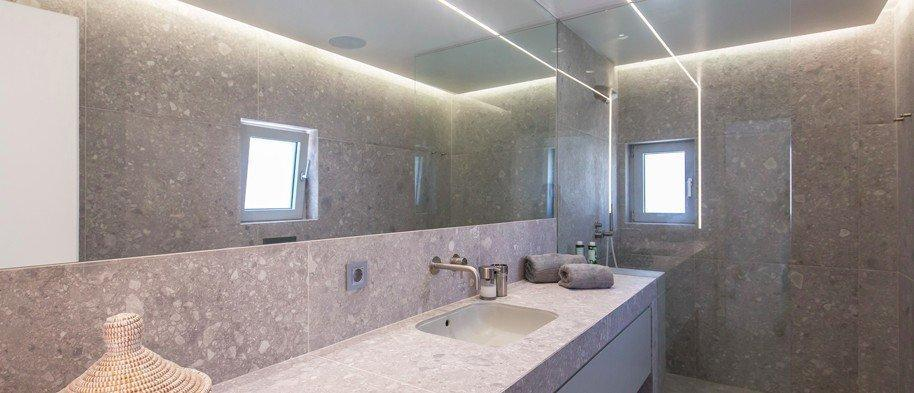 spacious bathroom with luxurious gray tiles and glass shower