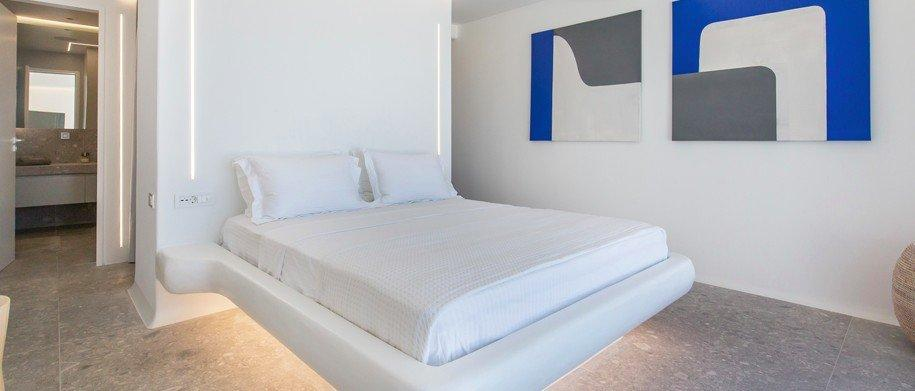 white walls of room with decorative picture and comfortable bed