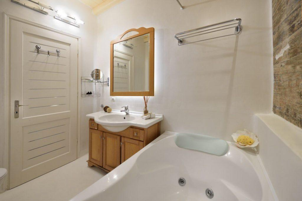 bathroom with wooden frame mirror and towel rack