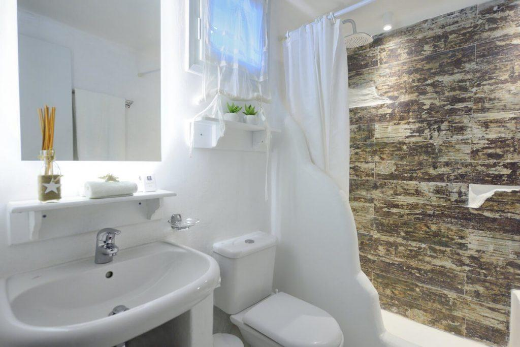 bathroom with tiled walls in shower and small window