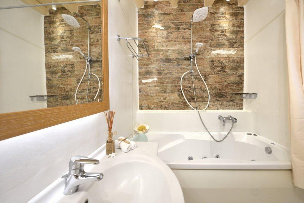 modern designed bathroom with bath and jacuzzi in one with tiled wall