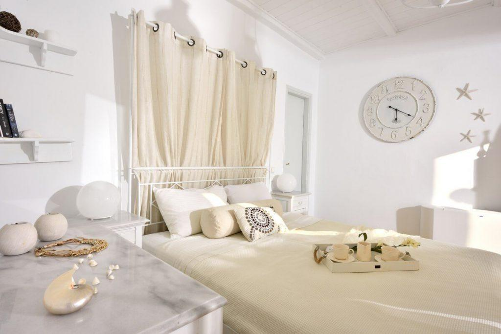 bedroom with beige sheets wall clock and curtain above bed