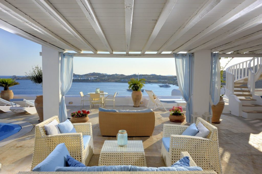 Villa Blue Ornos Mykonos Lounge area, sofa, coffee table, palm tree, rest area, flower decoration, panoramic view