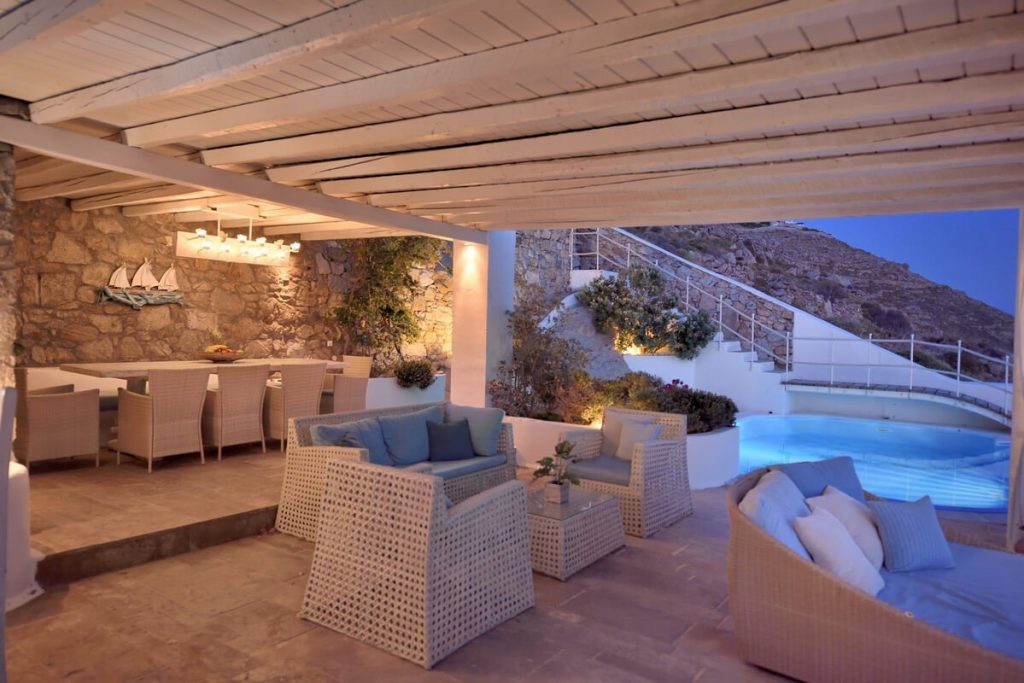 Villa Blue Ornos Mykonos lounge area, swimming pool, sofas, coffee table, outdoor dinner area