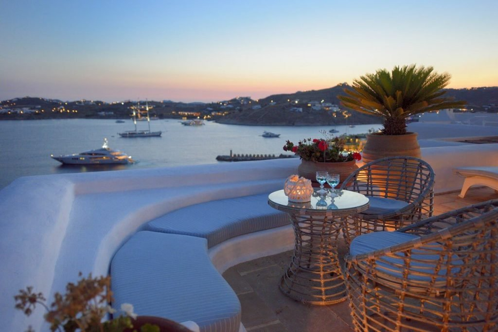Villa Blue Ornos Mykonos Panoramic view at the night, yacht, coffee table, wine glasses, palm tree, 2 chairs, coffee table