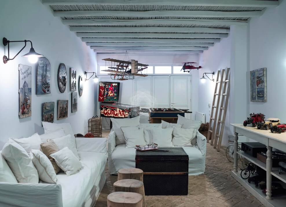 Villa Kassandra Agios Lazaros Mykonos living room, decorations, many art pictures on the wall, lamps, airplane models