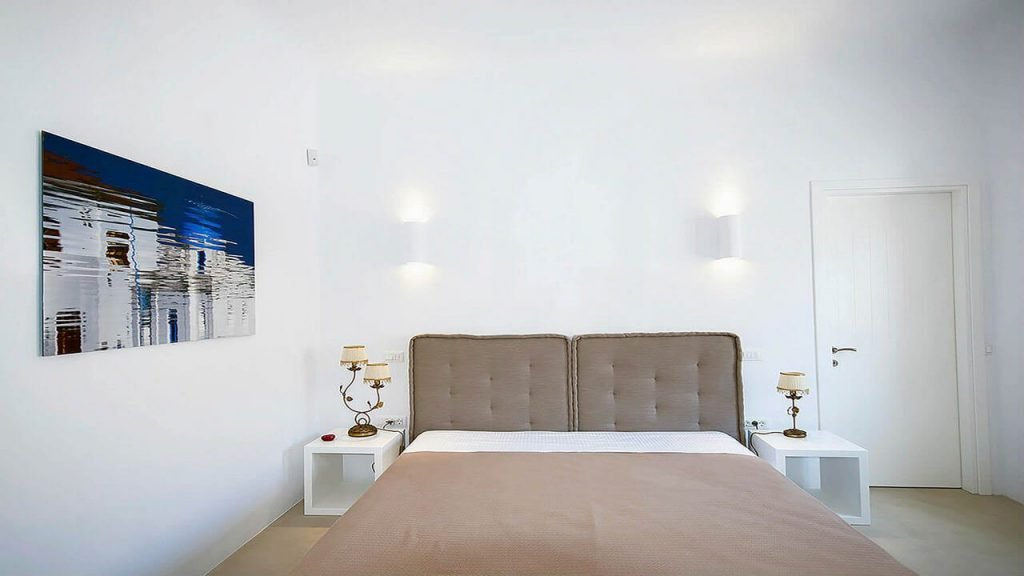 Villa Soto Houlakia Mykonos 4th bedroom with picture on the wall and door at the other wall