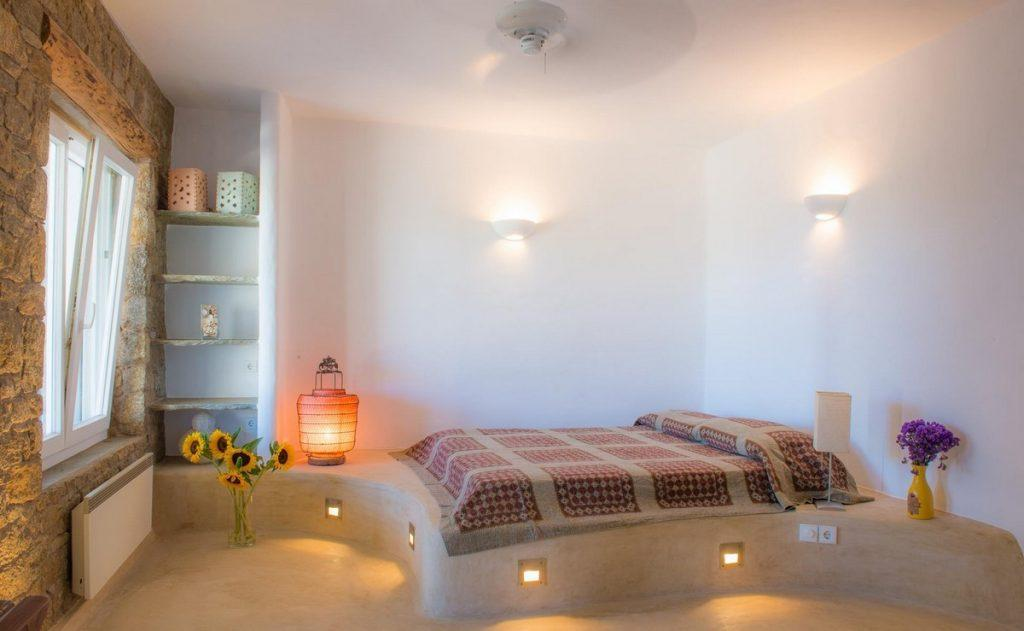 bedroom with lit above bed and wall lamps