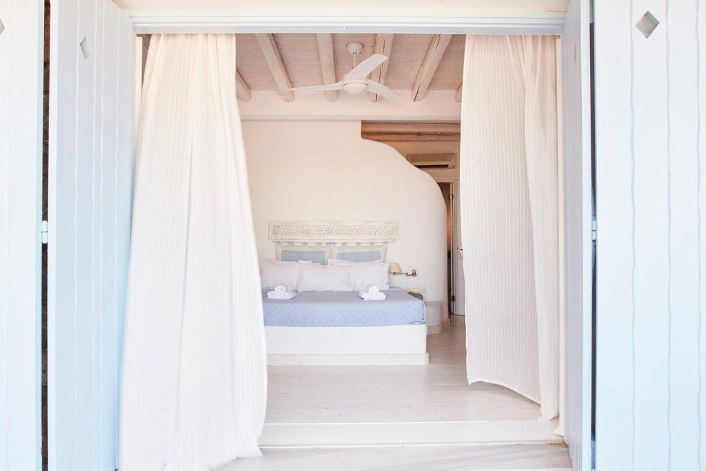 bedroom with blue bed sheet and fan to cool down
