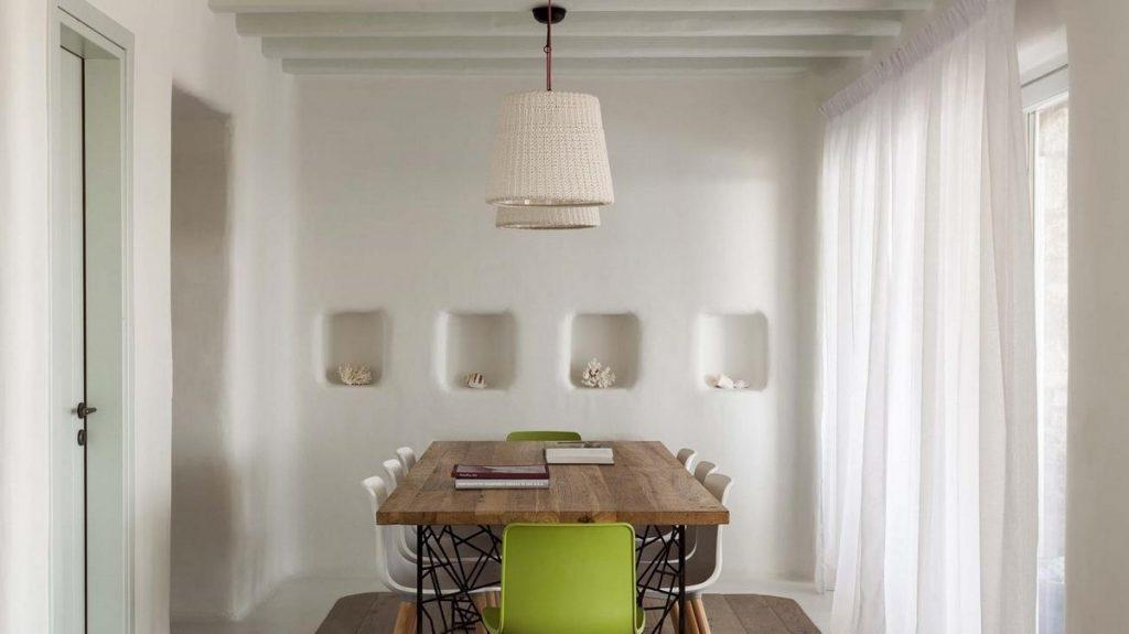 dining area with wooden table and white chairs
