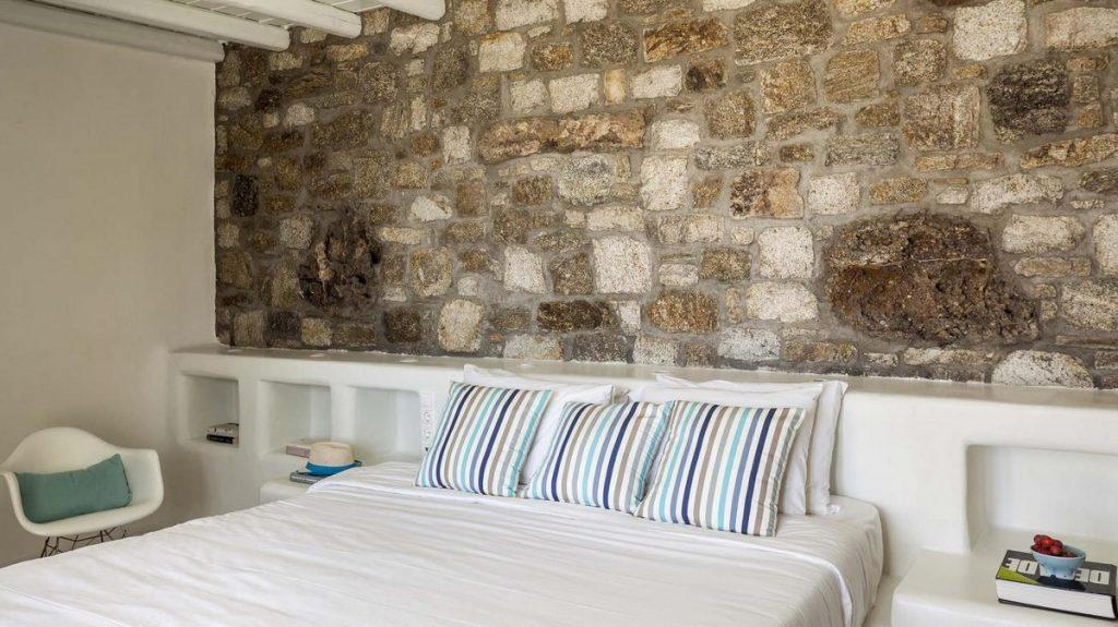 bedroom with stone wall and corner white chair