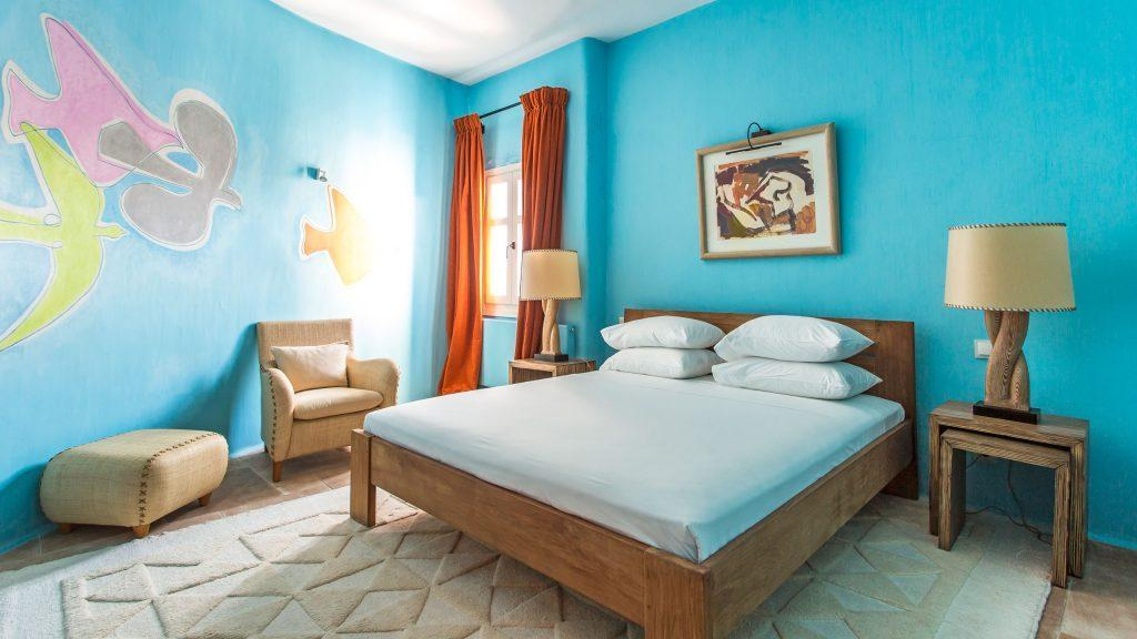 bedroom with nice paint on wall and huge lamps on wooden stands