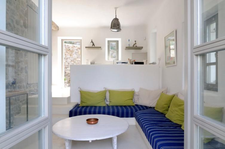 tucked in living space with corner cozy couch extra cushions and round table