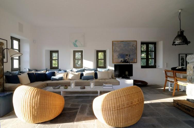 spacious living room with white sofa extra cushions table and lazy bags to chill and watch TV