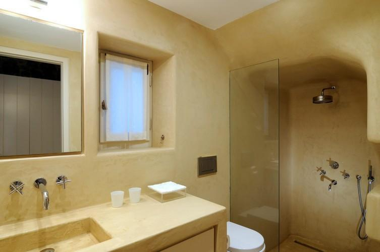 spacious led lamp illuminated bathroom with giant wall integrated shower cabin